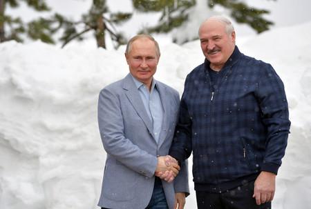 22日、ロシア南部ソチで、握手するロシアのプーチン大統領(左)とベラルーシのルカシェンコ大統領(EPA時事)