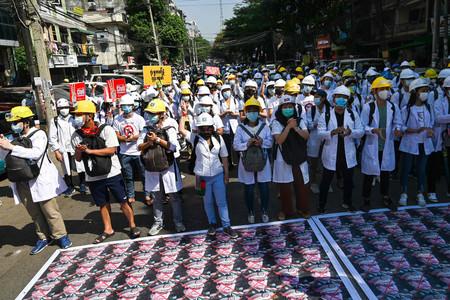 5日、ミャンマー最大都市ヤンゴンで、クーデターを起こした国軍への抗議デモを行う医療従事者や学生ら(AFP時事)