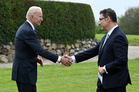 10日、英コーンウォールで握手するバイデン米大統領(左)とファイザーのブーラ最高経営責任者(CEO)(AFP時事)